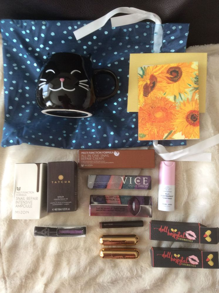 Skin care, lipsticks/glosses, a lovely black cat mug and a card